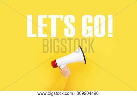 Megaphone In Hand And Inscription Let's Go On A Yellow Background