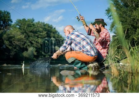 Big Game Fishing. Summer Weekend. Two Fishermen Relaxing Together With Beer While Fishing On Lake At