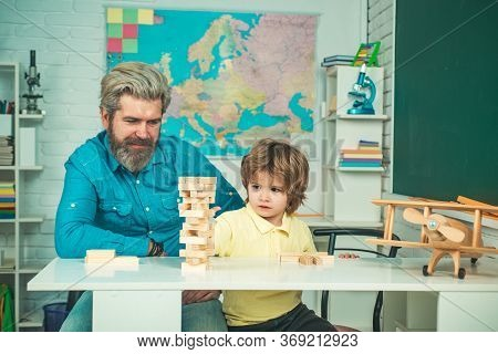 Smiling Father And Focused Son Playing Jenga Game At Home. Learning Concept. Afterschool Tutoring