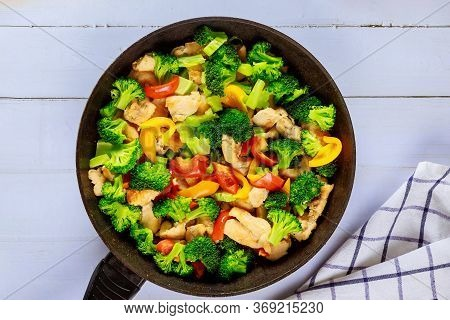 Vegetable Dish Stir Fry With Chicken In Pan On White Wooden Surface.