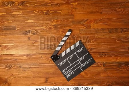 Movie Production Clapper Board Over Wooden Background. Top View. Copy Space.