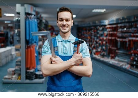 Worker holds hammer and corner in tool store