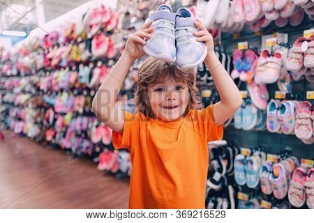 Kids Shopping. Sale, Consumerism And People Concept. Kids Shoes Store In Supermarket, Choosing Kids