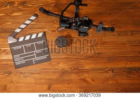Movie Production Clapper Board Over Wooden Background. Video Equipment. Top View. Copy Space.
