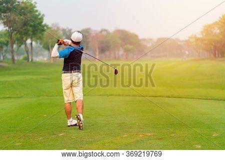 Man Golfer Hitting Ball With Club On Beatuiful Golf Course.