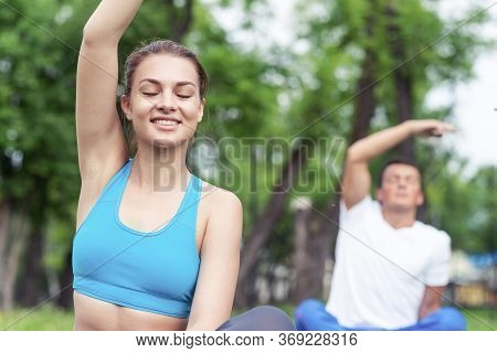 Young Couple Doing Yoga In Park Together. Man And Woman Sitting In Yoga Pose On Green Grass. Trainin