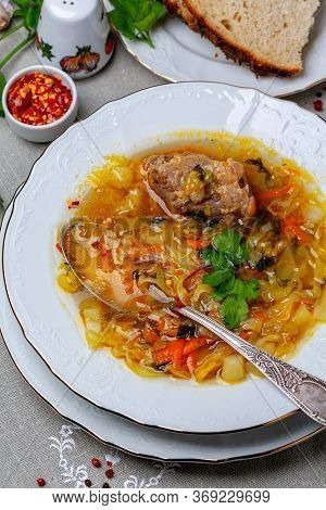 Soup Of Fresh Cabbage, Vegetables And Oxtails In A White Plate On A Linen Napkin. Top View.