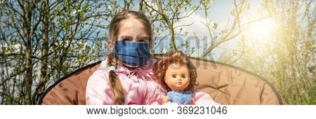 Schoolgirl With Plait In Mask Holds Doll Sitting In Armchair Against Green Trees And Bright Back Spr