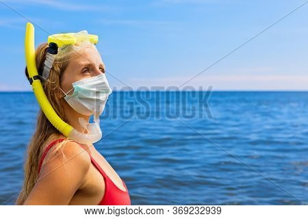 Girl In Snorkeling Mask Wear Surgical Face Mask On Sea Beach. Cancelled Cruises, Tours Due Coronavir
