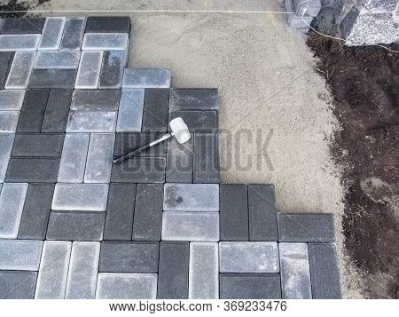 Laying Paving Brick Slabs On A Dry Cement-sand Mix, Top View. Rubber Mallet Lies On The Surface Of G