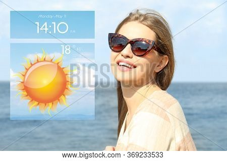 Young Woman Wearing Stylish Sunglasses Near River And Weather Forecast Widget. Mobile Application