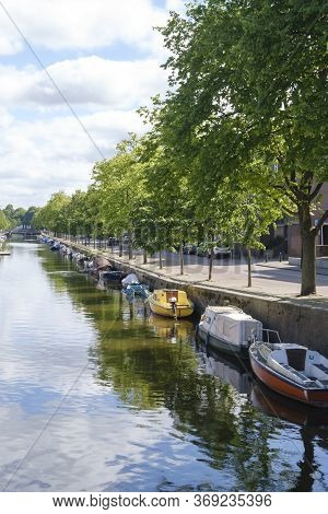 The Hague, The Netherlands - May 15 2020: Canal With Reflection Of Boats And Trees, Street Filled Wi