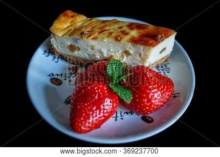 Piece Of Homemade Cheesecake On A Plate Decorated With Fresh Strawberries And Mint Leaves On A Black