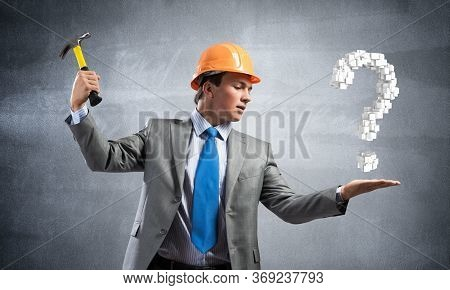 Businessman Going To Crash With Hammer Question Mark. Young Handsome Man In Business Suit And Safety