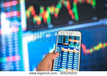 Blurred Background Of Monitoring Investment Stock Or Money Exchange On Smartphone In Hand.saving, In
