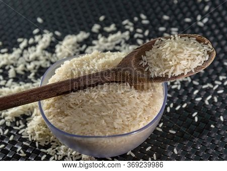 Grains Of Cereal Rice On A Dark Background In A Jar Next To Wooden Spoon