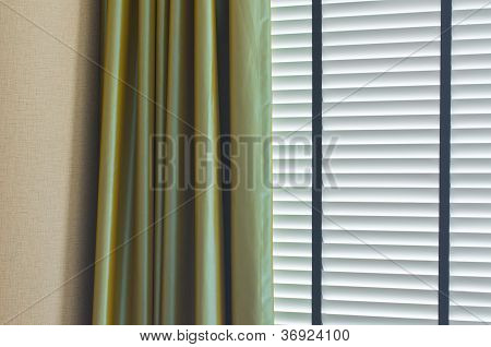 white closed jalousie and green curtain at day illumination