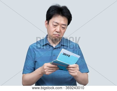 A Middle-aged Asian Man Holding A Bank Passbook In His Hand On A Gray Background.