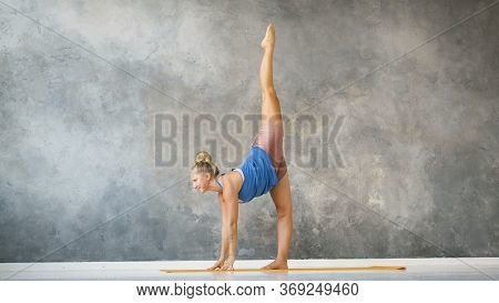 Young Yoga Trainer Doing Stretching Exercises On A Yellow Rug In A Loft Studio Slow Motion