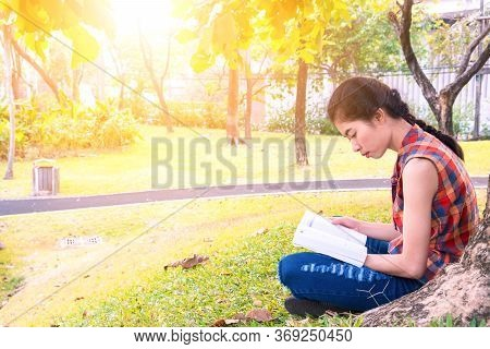 Asian Women Sitting Reading Under Tree At Public Park Relax And Intend To Study Knowledge In The Hol