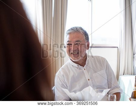 A Handsome Older Man Smilng Off The Camera In A Social Situation