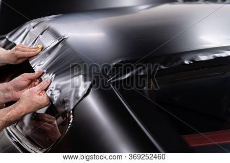 Man Worker In Car Detailing Studio Applying Color Changing Vinyl Foil On Car.