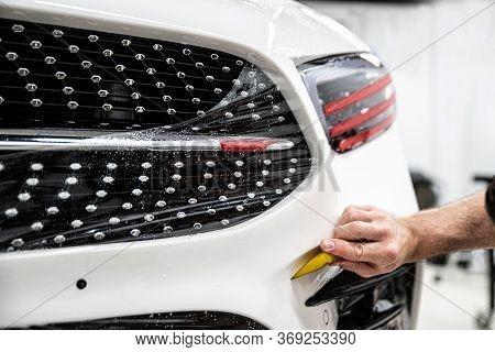 Car Wrapper Applying Protective Transparent Foil On Car Body.
