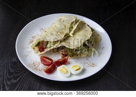 Sliced chicken With Canned  Cucumbers And Cabbage In Sauce, Wrapped In Pita Bread On A White Plate