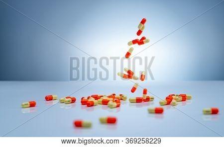 Yellow-orange Capsules Pill Falling Down On White Table. Pharmaceutical Industry. Tranexamic Acid Ca