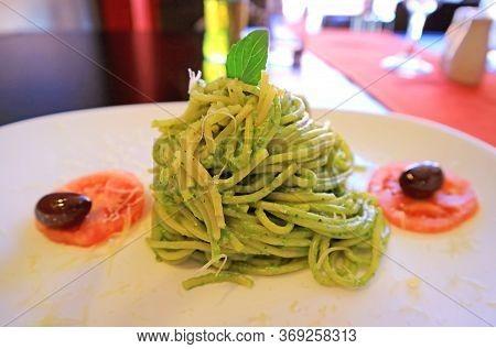 Closeup A Plate Of Delectable Spaghetti In Pesto Sauce