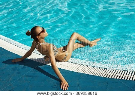Back View Tanned Woman In Bikini And Sunglasses Relaxing And Sunbathing Near Swimming Pool.