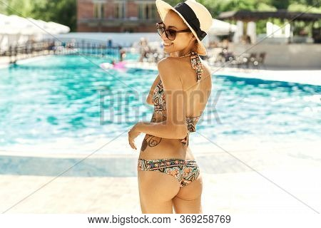 Back View Woman With Tanned Sexy Body In Bikini And Hat Posing Against Poll, Summer Background.