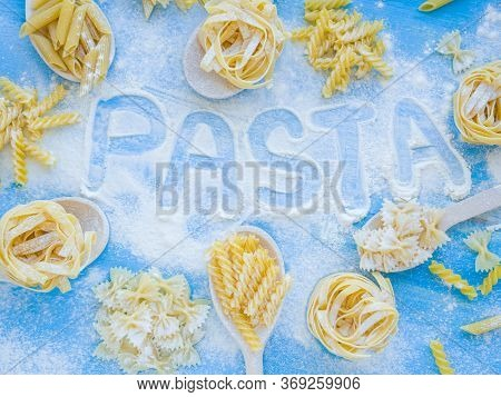 Word Pasta On Wooden Table With Variety Of Types And Shapes Of Dry Italian Pasta And Flour. Pasta In