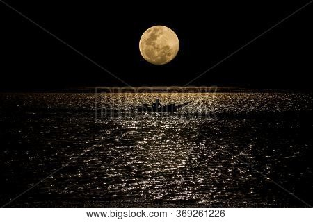 The Full Moon Floats Past The Edge Of The Water On A Completely Dark Night, Making The Boat Passing