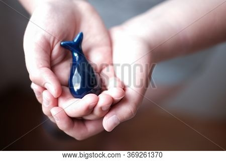 Human Hands Holding Blue Whale. Save Whales And Protect Nature. Eco Activism Concept. Ceramic Blue W