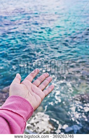Female Hand With An Open Palm Reaches For Surface Of The Water. Ocean Protection Concept. World Ocea