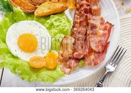English Breakfast-plate With Fried Bacon, With French Fries, Fried Egg Stands On A White Table And A