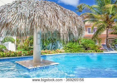 Pool At A Beautiful House Surrounded By Tropical Greenery On A Sunny Day. In The Pool With  Umbrella
