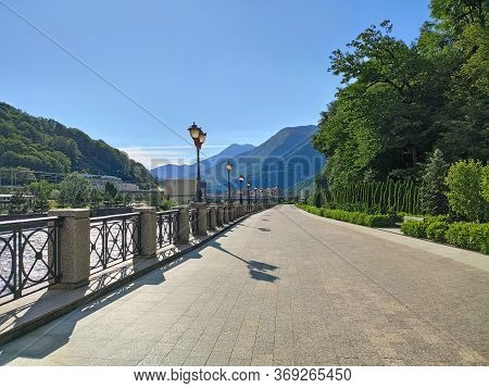 Walking Promenade With Paving Slabs And Ornamental Trees At Mountains Background. Sunny Day In Krasn