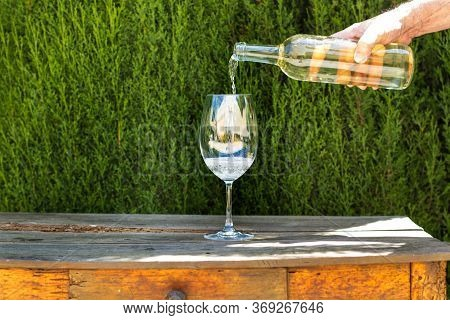 Man Pouring A Glass Of White Wine On A Wooden Table With A Cypress Tree Behind