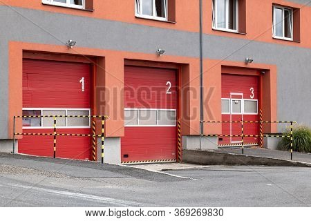 Red Entrance Gates To A Czech Fire Station Where The Fire Trucks Are Parked And Ready For Emergency
