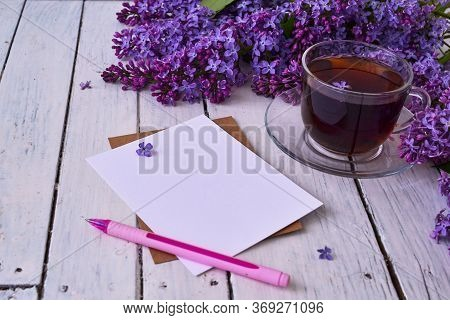 Cup Of Tea With Lilac Flowers On A Wooden White Background. Nearby Lies A Sheet Of Paper, And A Pink