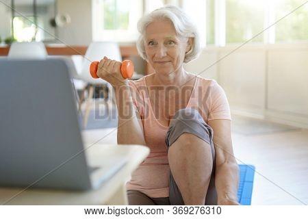 Senior woman doing fitness exercises at home through virtual class
