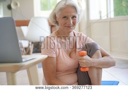 Senior woman doing fitness exercises with virtual class
