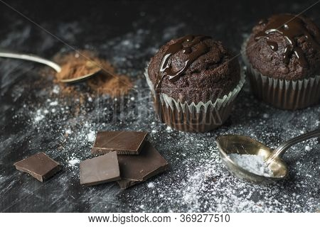 Close Up Of Cocoa Muffins With Chocolate Icing On Rustic Table Covered With Sugar And Cocoa With Vin