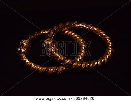 Indian Traditional Gold Bangles Isolated On A Dark Background . Indian Traditional Gold Ornaments