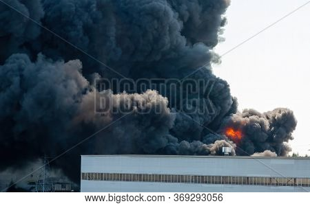 Black Plumes Of Smoke From An Accidental Toxic Industrial Fire As Seen From A Behind A Factory Build