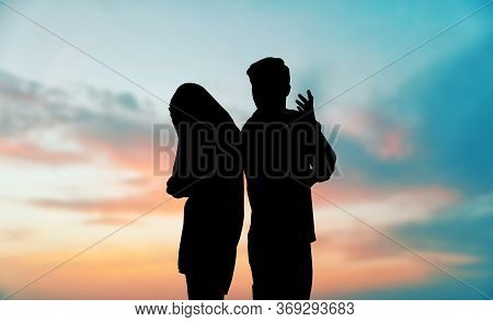 Silhouettes Of Arguing Couple Against Sunset Sky With Clouds. Relationship Problems