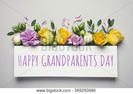 Flat Lay Composition With Beautiful Blooming Flowers And Phrase Happy Grandparents Day On Grey Backg