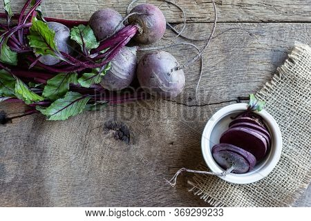 Bunch Of Fresh, Spring, Organic Beetroot On Kitchen Grid, With Slices Of Beetroot In Ceramic Plate O